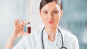 A doctor holding a small jar of CBD oil.
