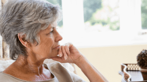 A senior woman sitting, lost in thought.