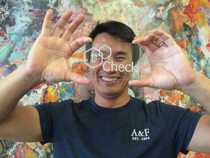 happy man holding a tCheck logo