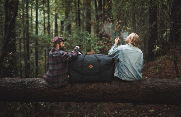 two travelers enjoying a smoke on a log with a reverly bag between them